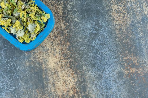 Pétales de chrysanthème séchés sur plaque bleue.