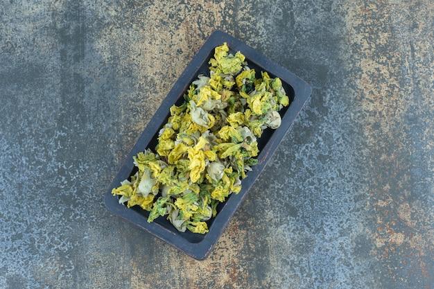 Pétales de chrysanthème séchés sur plaque noire.