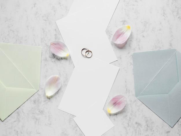 Pétales de fleurs à côté des bagues de fiançailles
