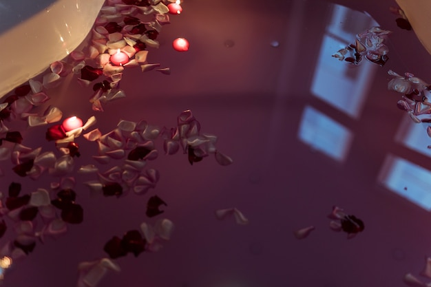 Pétales de fleurs sur l'eau près des bougies allumées dans la baignoire spa