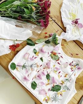 Pétales de fleurs et feuilles sur un tapis sur une surface en bois