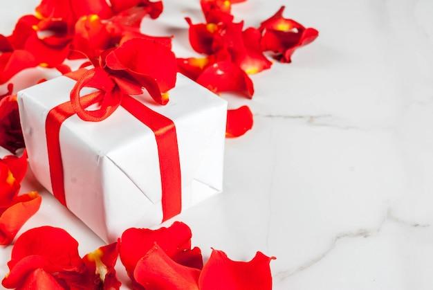 Pétales de fleurs roses et coffret cadeau enveloppé blanc avec ruban rouge sur fond de marbre blanc