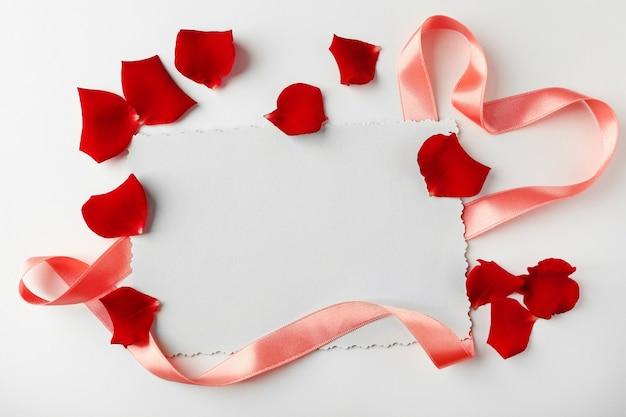 Pétales de fleurs avec ruban de soie et carte isolated on white