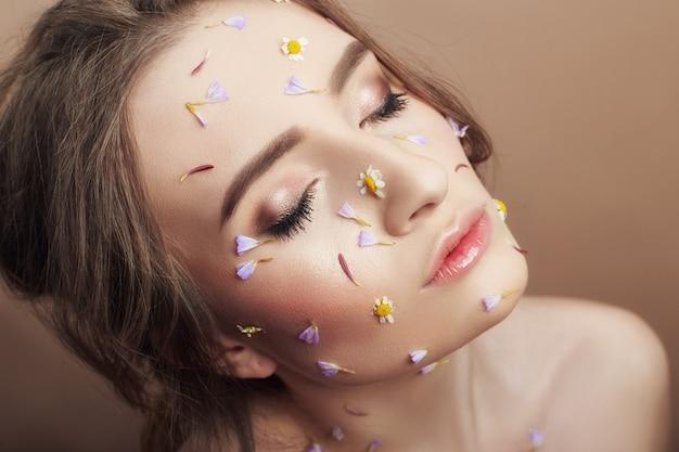 Pétales de fleurs sur le visage fille, peau femme cosmétiques