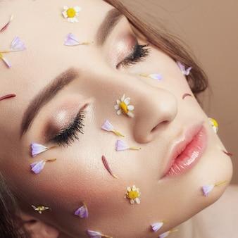 Pétales de fleurs sur le visage fille, visage femme cosmétiques