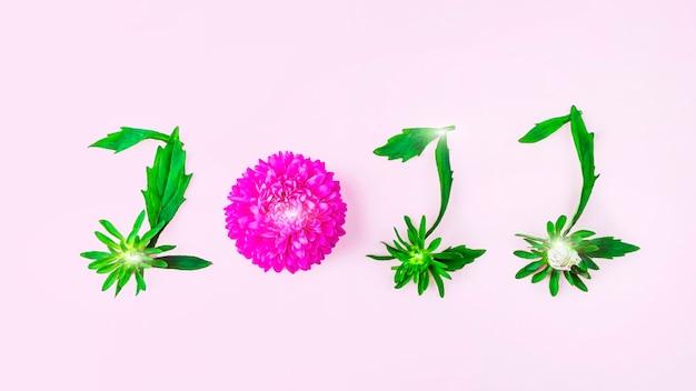 Pétales floraux et feuilles sous forme de nombres 2022. inscription sur fond rose. notion de nouvel an.