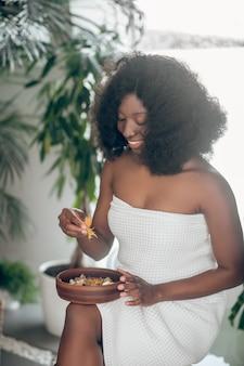 Pétales de plantes, spa. jeune femme bouclée aux cheveux longs à la peau foncée avec les épaules nues tenant un plateau de pétales dans un salon de spa