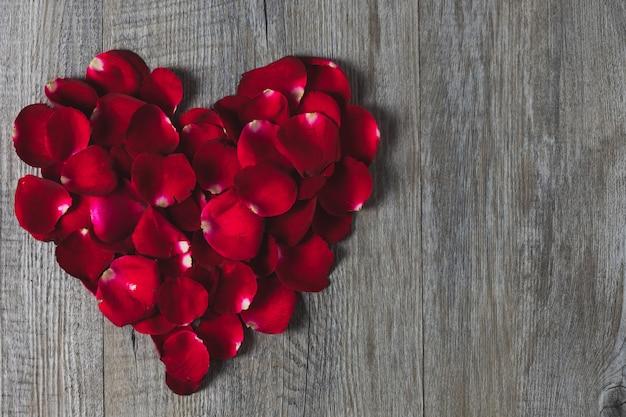 Pétales de rose disposés en forme de cœur. placé sur un plancher en bois gris, vue de dessus, thème de la saint-valentin