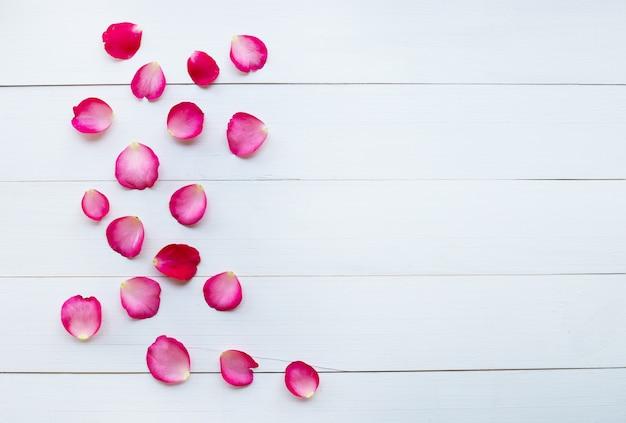 Pétales de rose sur fond en bois blanc.