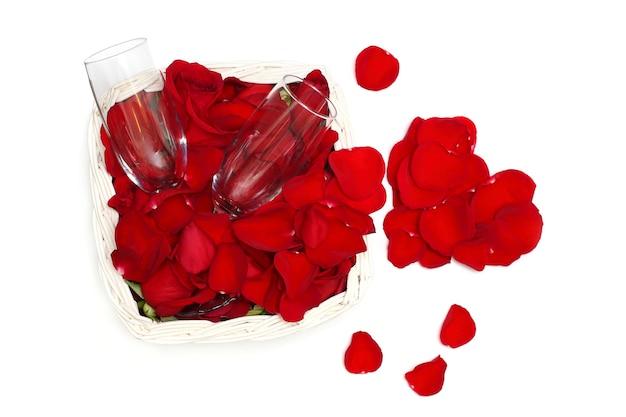 Pétales de rose, forme de coeur et deux verres de vin comme concept d'amour