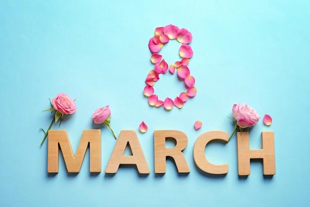 Pétales de rose et lettres en bois. composition de la journée internationale de la femme