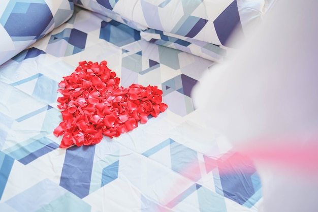 Pétales de rose rouges disposés en forme de coeur sur un lit de couple.