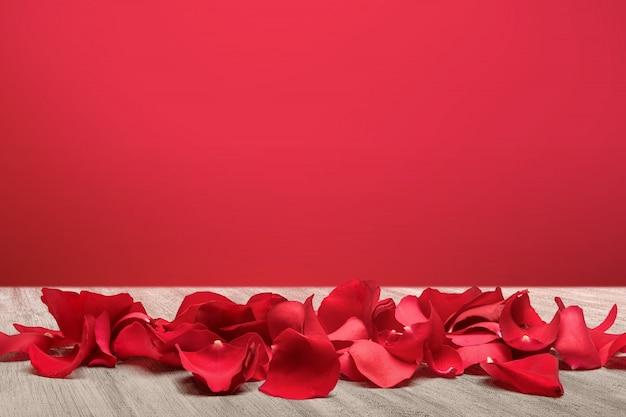 Pétales de rose rouges sur fond de plancher en bois