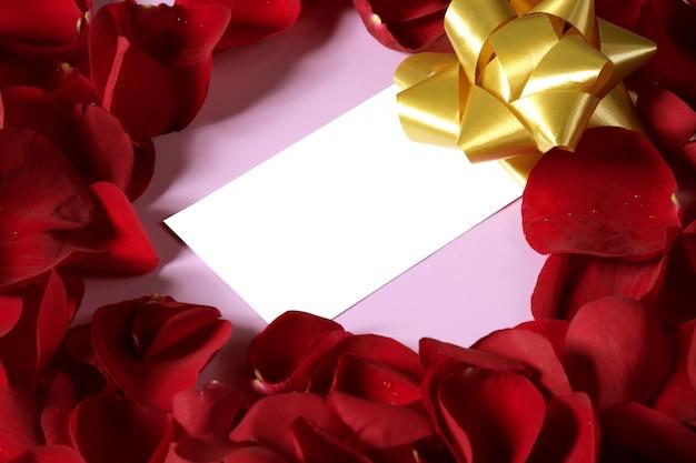 Pétales de rose rouges en forme de coeur, note vide espace copie