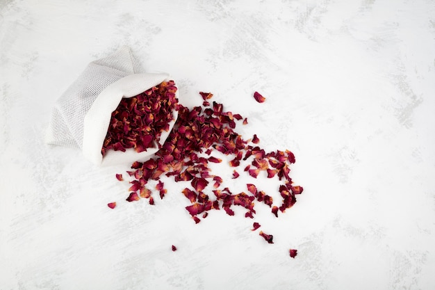 Pétales de rose séchés dans une pochette vue de dessus pétales secs rouges