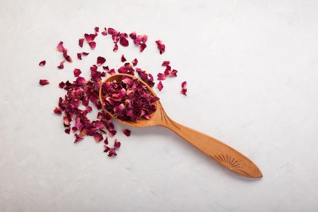 Pétales de rose séchés en vue de dessus de cuillère en bois