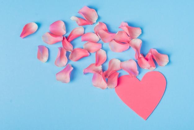 Pétales de roses avec coeur rose sur table