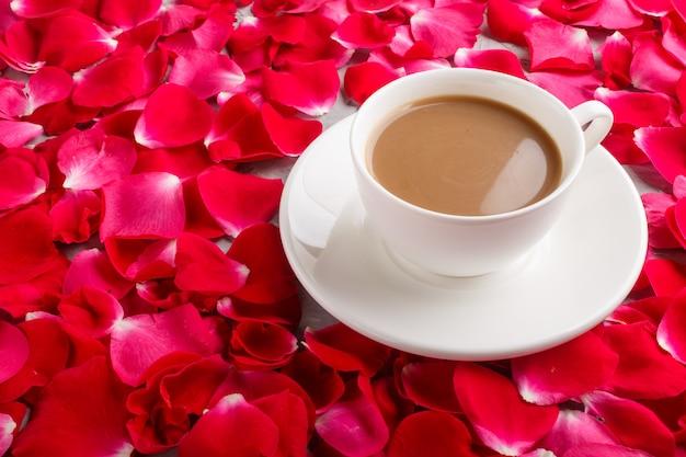 Pétales de roses rouges et une tasse de café. vue de côté.