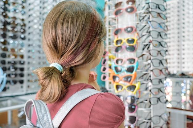Petit acheteur dans le magasin de lunettes, une petite fille choisit des lunettes de soleil
