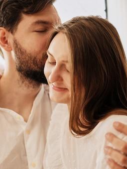 Petit ami aimant embrasse l'oreille de sa petite amie. embrasser doucement baiser. les amants sont habillés en pyjama