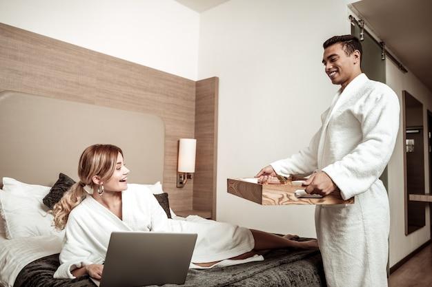 Petit ami attentionné. petit ami rayonnant attentionné apportant le petit déjeuner au lit pour sa petite amie attrayante