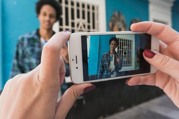 Petit ami à l'écran smartphone devant la maison bleue