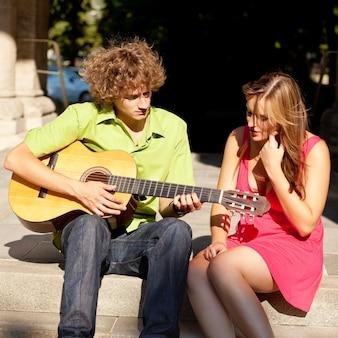 Petit ami jouant un chant de guitare à sa petite amie