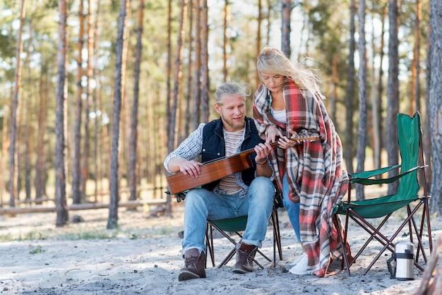 Petit ami jouant de la guitare acoustique dans la forêt