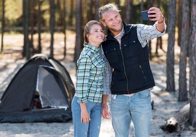 Petit ami prenant un selfie avec leur tente à l'arrière