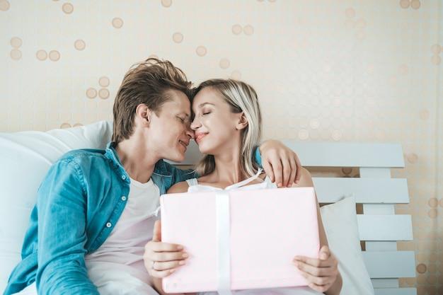 Petit ami surprend sa copine avec une boîte cadeau sur le lit