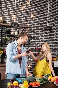 Petit anniversaire. jeune couple rayonnant d'amour faisant claquer leurs verres avec du vin célébrant le petit anniversaire
