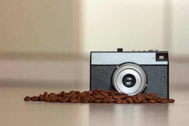 Petit appareil photo vintage à l'ancienne et grains de café sur flou