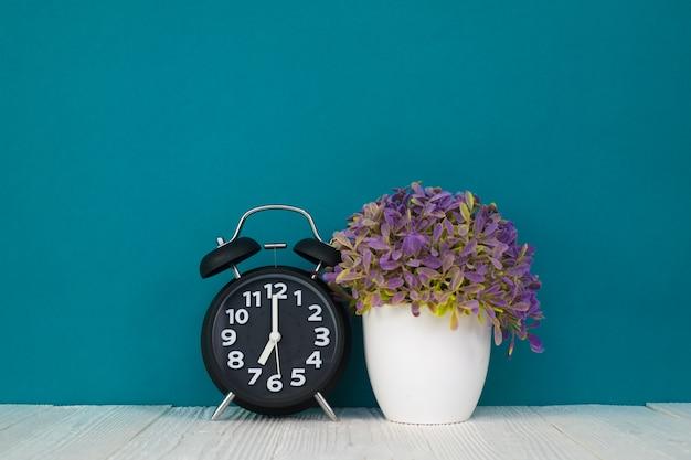 Petit arbre et bouquet de fleurs avec réveil vintage sur bois