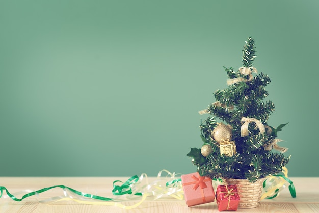 Petit arbre de noël et des boîtes avec des cadeaux sur une table en bois.