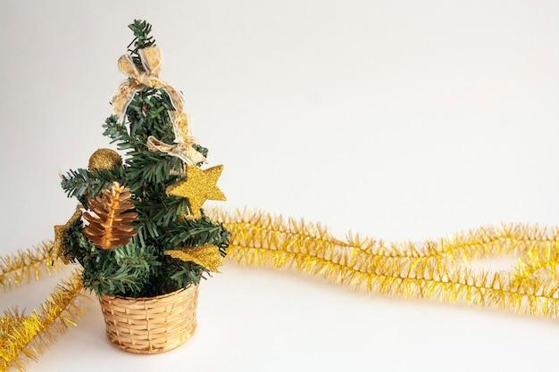 Petit arbre de noël avec des jouets dans un panier et des guirlandes, isolé, copiez l'espace