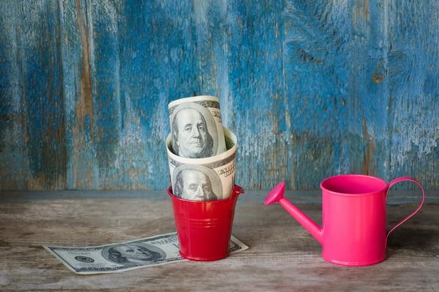 Petit arrosoir et dollars en pot. vieux fond en bois. concept d'entreprise