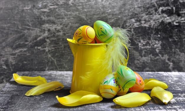 Petit arrosoir jaune avec des oeufs de pâques sur fond de bois