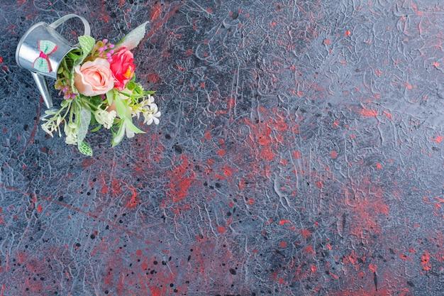 Un petit arrosoir métallique plein de beau bouquet de fleurs .