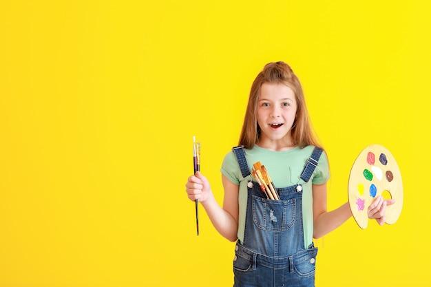 Petit artiste mignon sur la surface de couleur