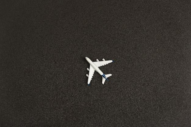 Petit avion jouet sur fond noir. vue de dessus.