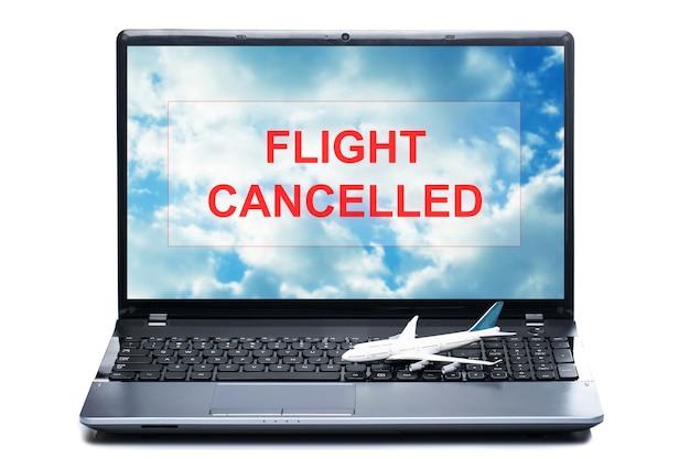 Petit avion jouet sur un ordinateur portable avec un message - vol annulé