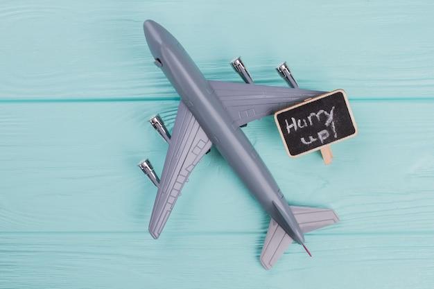 Petit avion en plastique gris et petite plaque signalétique sur fond bleu avec espace de copie. fond texturé en bois.