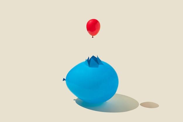 Un petit ballon de fête rouge sort d'un grand bleu fissuré sur fond jaune. concept abstrait minimal. disposition isométrique. rectangle avec espace de copie.