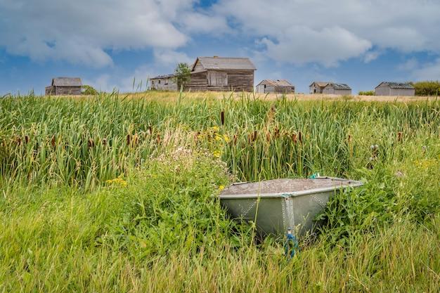 Petit bateau en aluminium avec une maison abandonnée dans une basse-cour dans les prairies canadiennes