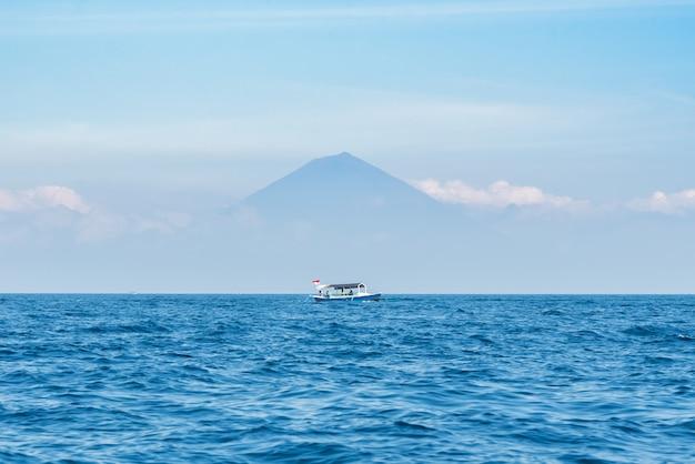Petit bateau en bois sur un océan bleu avec ciel dégagé et le mont agung sur fond.