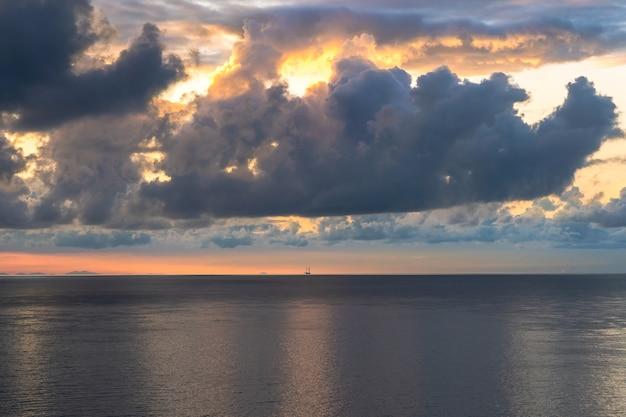 Petit bateau à l'horizon au lever du soleil avec des nuages incroyables