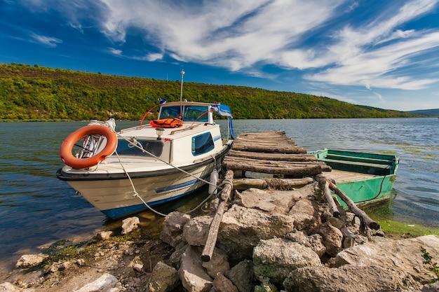 Petit bateau de pêche à l'aviron amarré sur une rivière avec réflexion