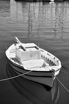 Petit bateau de pêche blanc. photographie en noir et blanc. héraklion, grèce