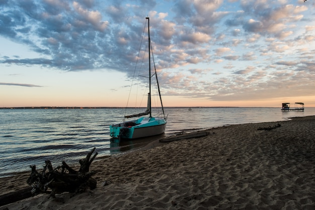 Petit bateau de pêche sur la plage avec coucher de soleil le matin