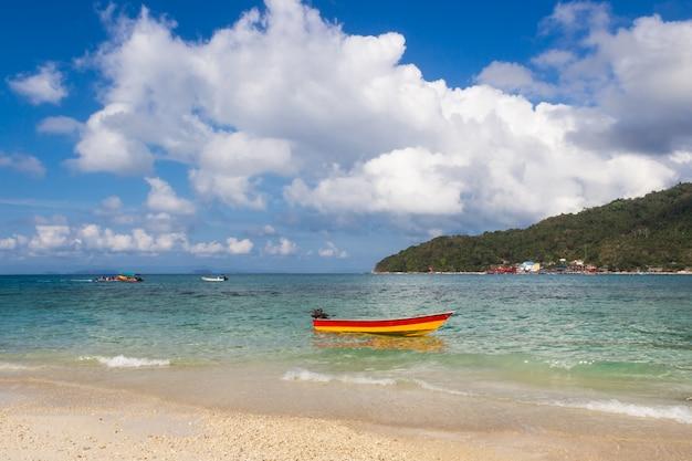 Petit bateau près de la côte et ciel nuageux.